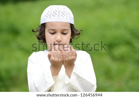 A little Arabic boy praying outdoor in nature - stock photo