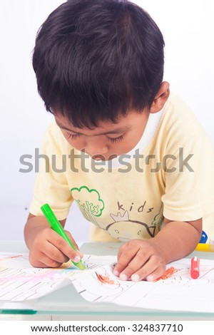 a little asian boy paint color on white paper on white background - stock photo