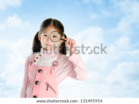 A little Asian girl peers at the camera through a magnifying glass in summer day, blue sky background - stock photo
