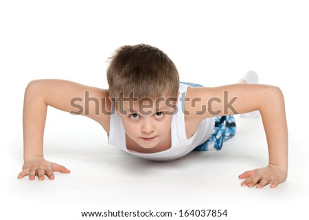 A little athletic boy is pushing up on the white background