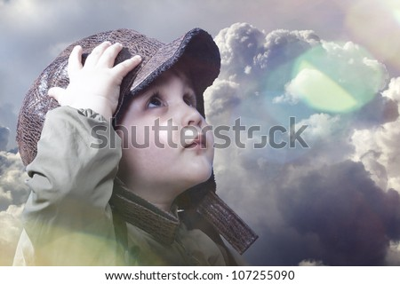 A little baby boy dreams of becoming a pilot. Sunburst and lens flare - stock photo