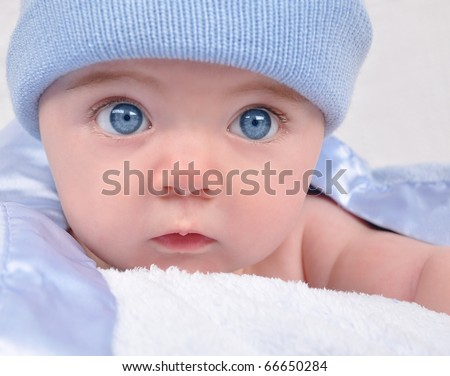 A little baby boy with blue eyes is staring with a hat. The child is on a blanket.