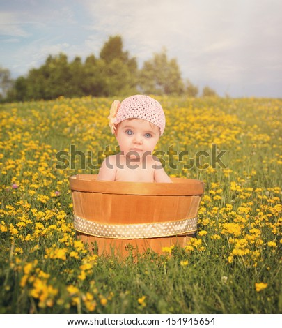 A little baby girl is sitting in a wooden basket outside with yellow flowers on a hill for a love or nature concept.