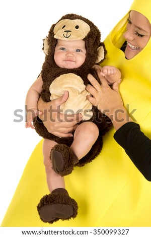 A little baby in her monkey costume with her mom dressed up as a banana.