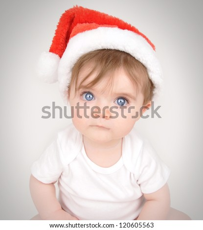 A little baby is sitting down and looking into the camera with big blue eyes and a santa christmas hat on.