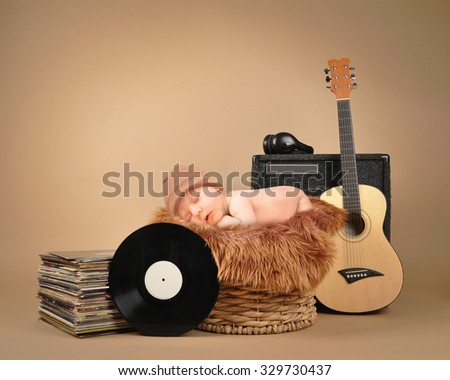 A little baby is sleeping in a basket with music headphones and retro vinyl records on an isolated tan background for a party or entertainment concept.