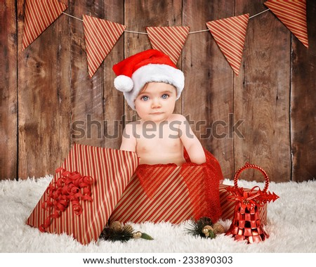 A little baby is wearing a red christmas santa hat and sitting in a present with a wood backdrop for a season or portrait concept.
