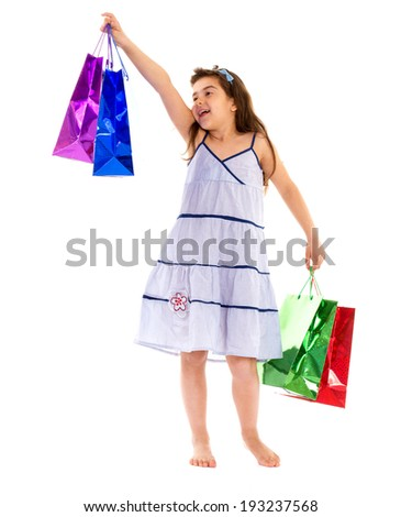A little barefooted girl with colorful bags in their hands on a white background