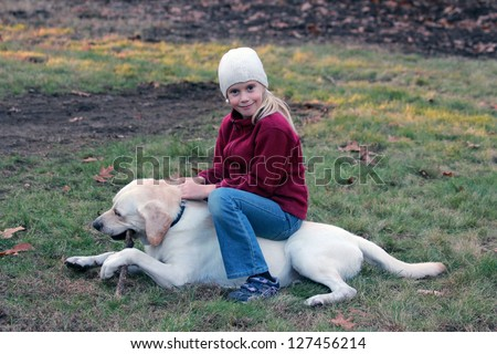 A little blond girl playing with her pet dog in autumn park Golden retriever - stock photo
