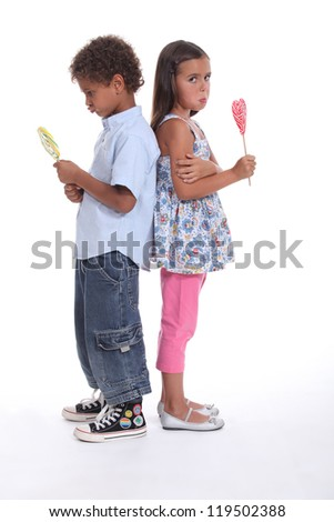 a little boy and a little girl pouting and eating ice cream - stock photo