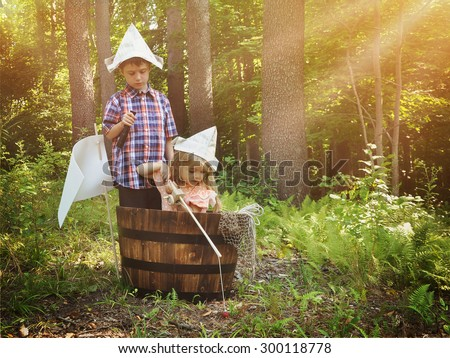 A little boy and girl are pretending to fish in a wooden barrel boat in the nature woods with a real fish being caught by the children for an imagination or creativity concept. - stock photo