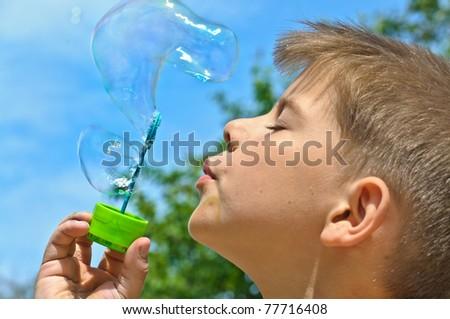 A little boy blows bubbles. Background sky.
