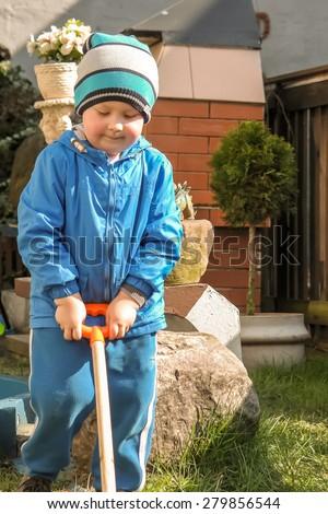 A little boy doing spring yard work - stock photo