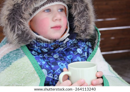 A little boy holding a cup in nature. A child in a jacket with a hood and wrapped in a plaid. The baby's face close-up and in focus. A boy is lonely and his sad face looking far away. - stock photo