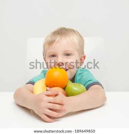 A little boy hugging fruit against a white background - stock photo