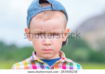 A little boy in a cap and a multicolored plaid shirt sad looks away. Family composition