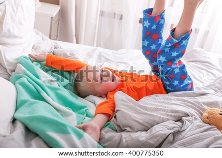 A little boy in a pajama lying on the bed
