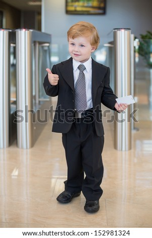 A little boy in a suit shows thumbs up at the entrance to the business center  - stock photo