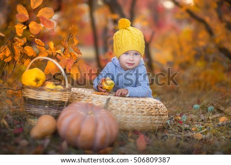 A little boy in a yellow hat sitting on a wicker pufe in the autumn forest with pumpkins and apples