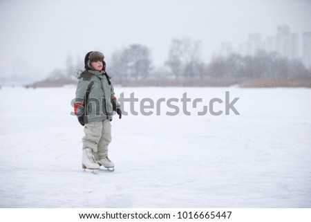 A little boy in huge skates is riding on the lake.Entertainment on a winter day for a child.