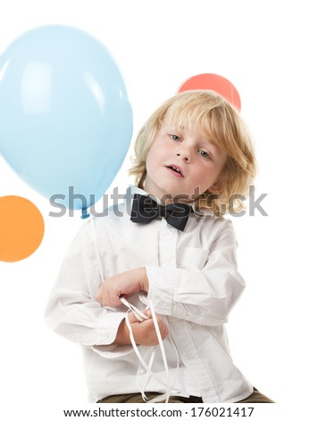A little boy is holding a blue balloon from a party.