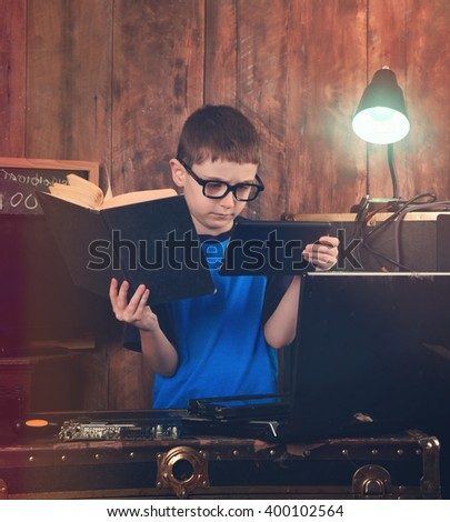 A little boy is reading a science book and holding an internet tablet with computer objects around him for an education or programming concept - stock photo