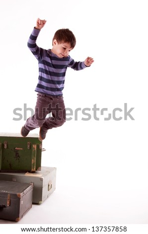 A little boy jumps from a boxes in the studio on a white background, selective focus on face - stock photo