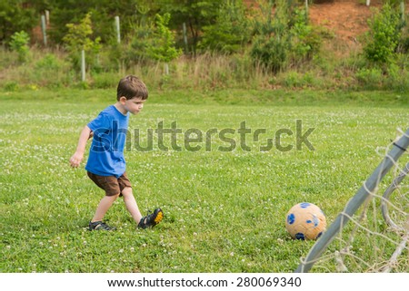 A little boy kicking a ball in the grass outside, near a soccer goal. Spring setting. Horizontal.
