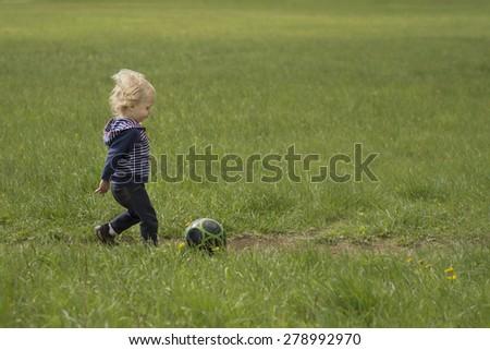 A little boy kicks a ball outside in a grassy meadow.  - stock photo