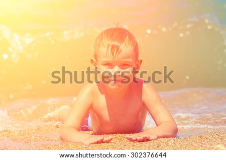 A little boy lies on a sunny day at the beach on the sea sand and smiling, and behind it a large sea wave. Vintage Family composition