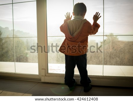 A little boy looking trough the window - stock photo