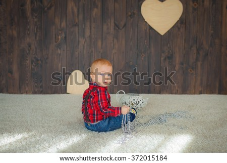 a little boy looks at the camera, wearing a red shirt, a photo shoot in the studio
