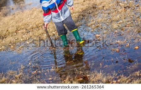A little boy playing with a stick in puddles wearing rain boots. - stock photo