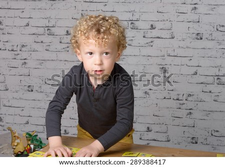 a little boy plays on a table with cards
