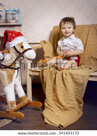 A little boy plays with a horse-rocking around the Christmas tree - stock photo