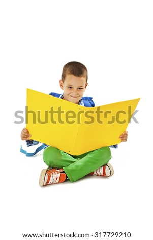 A little boy reading a big yellow book. Isolated on white background - stock photo