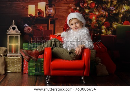 A little boy Santa Clause siting on red armchair on the Christmas  background.