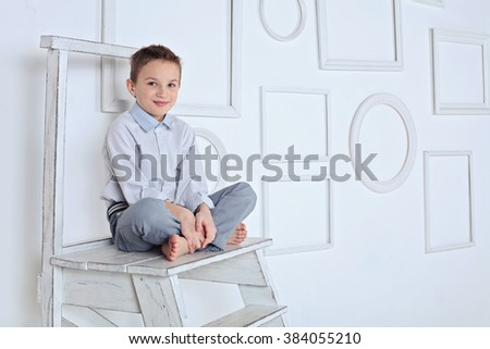 A little boy sit on the wooden stairs in white studio, looking at camera. Back to school. Children portrait. Stylish kid in suit