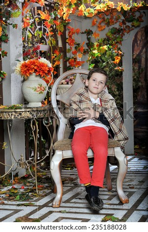 a little boy sits in a chair in a blanket in the garden in autumn - stock photo