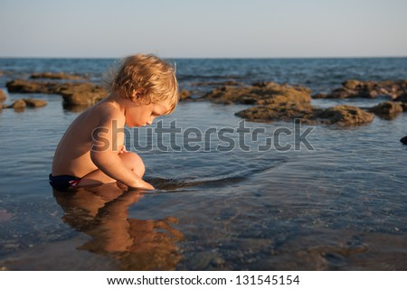 A little boy sits in the water at the beach - stock photo