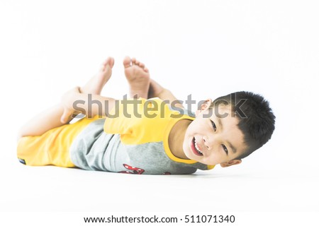A little boy sits on the floor against the white background