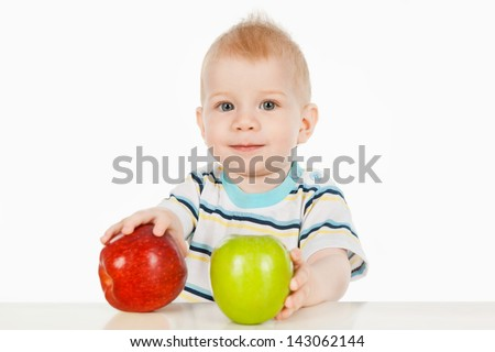 A little boy sitting at a table with two apples - stock photo