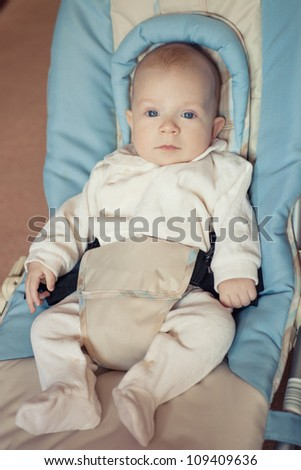 a little boy sitting in a child seat