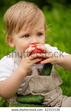 A little boy sitting on the grass and eating tomatoes. In pockets lie cucumbers. - stock photo