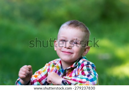 A little boy sitting on the grass and looking forward happily. Family composition - stock photo