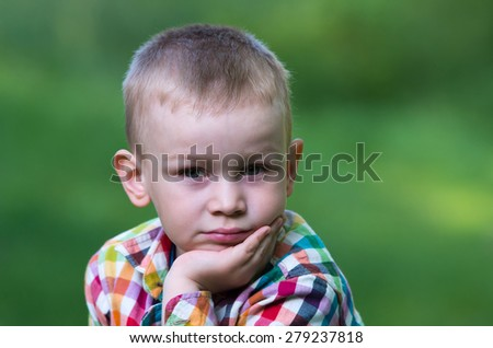 A little boy sitting on the grass and looking thoughtfully ahead. Family composition - stock photo