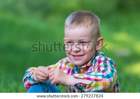 A little boy sitting on the grass and looks slyly to the side. Family composition - stock photo