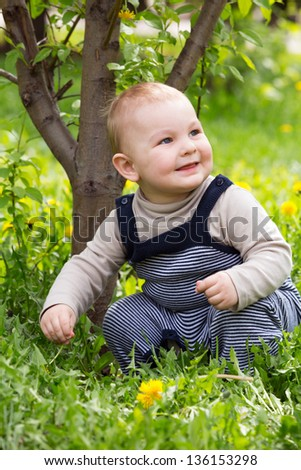 A little boy sitting on the grass and smiling. - stock photo