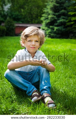 a little boy sittingin the grass and laughing - stock photo
