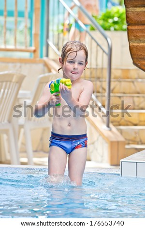 A little boy wading in the pool with a water gun. - stock photo